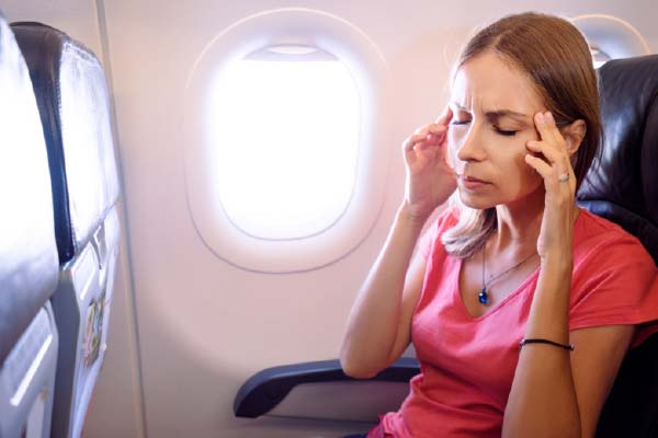 Woman on Plane Touching Temples