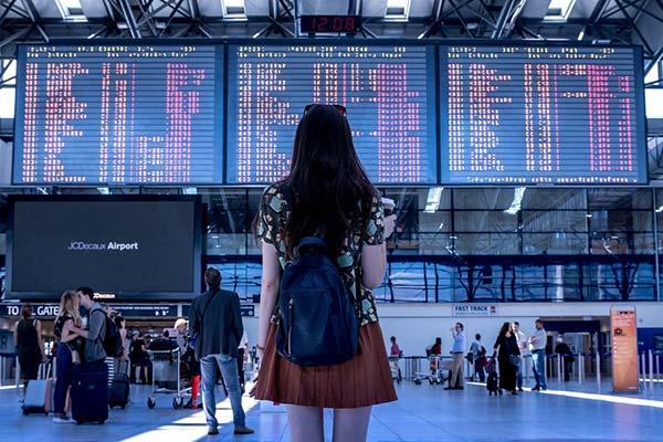 Girl Viewing Flight Departures Board