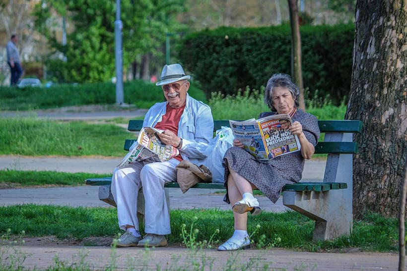 Old Couple Reading Papers on a Bench