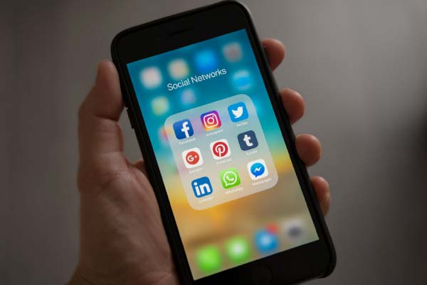 Holding iPhone with Social Media Apps