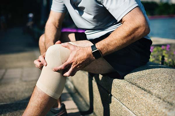 Holding Sore Bandaged Knee
