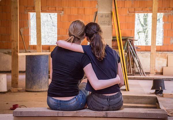 Two Girlfriends Sat Hugging