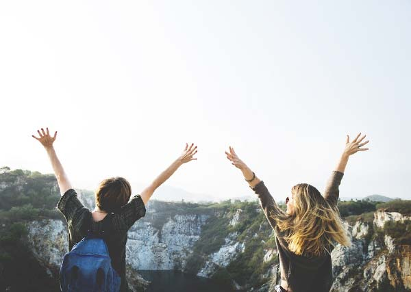Two Young Travellers Arms Outstretched