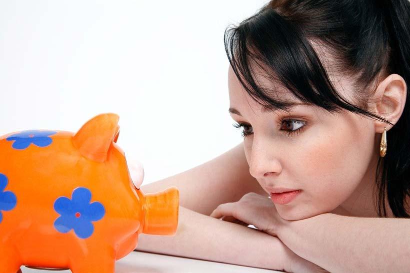 Girl Looking at Piggy Bank