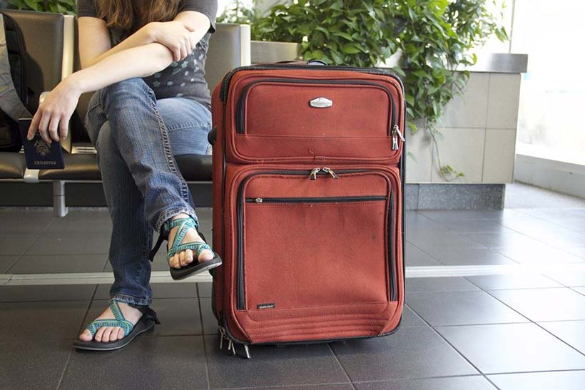 Girl Sat at Airport Gate with Suitcase